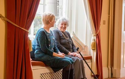 Two ladies sitting on a window seat with walking stick in view
