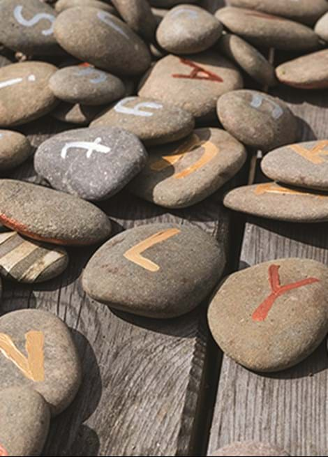 Pebbles painted with letters sitting on decking