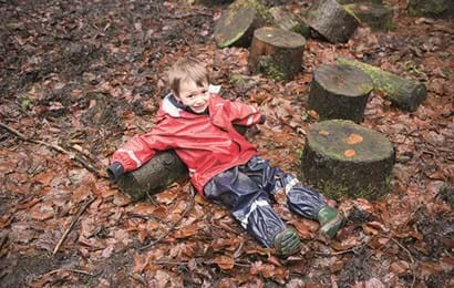 Boy lying on wet leaves
