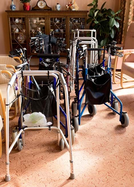 Different kinds of walking aids and chairs in a care home lounge