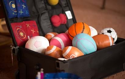 A suitcase containing different kinds of colourful balls and beanbags